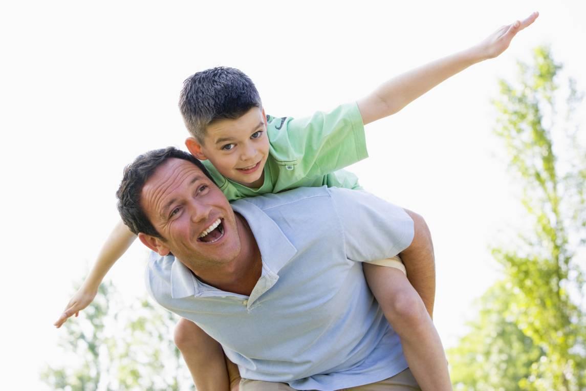 Man giving young boy piggyback ride outdoors